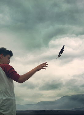 Mark Owen TEENAGE BOY RELEASING FEATHER NEAR MOUNTAINS Children