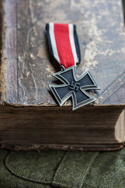 Stephen Mulcahey 1940s iron cross lying on leather book Miscellaneous Objects
