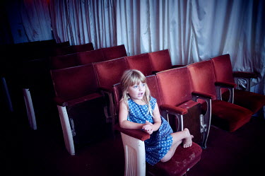 Stuart Brill LITTLE BLONDE GIRL SITTING IN THEATRE Children
