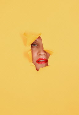 Rolf Brenner YOUNG WOMAN THROUGH HOLE IN YELLOW PAPER Women