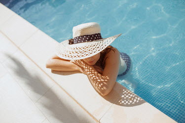 Nina Masic YOUNG WOMAN WEARING SUNHAT IN SWIMMING POOL Women