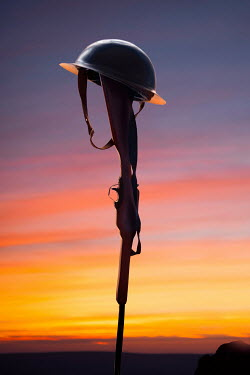 Lee Avison soldiers helmet on the butt of a rifle at sunset Weapons