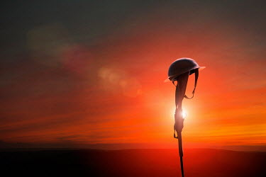 Lee Avison soldiers battle helmet on the butt of a rifle at sunset Weapons