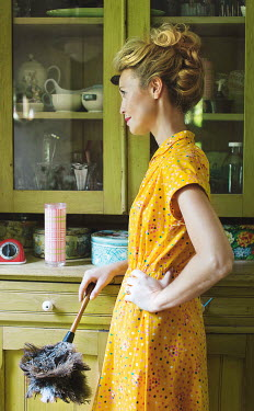 Robin Macmillan VINTAGE WOMAN WITH FEATHER DUSTER IN KITCHEN Women