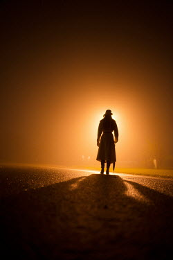 Terry Bidgood SILHOUETTE OF WOMAN IN FRONT OF CAR HEADLIGHTS Women