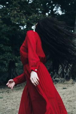 Alina Zhidovinova WOMAN WITH DARK HAIR WEARING RED DRESS BY TREES Women