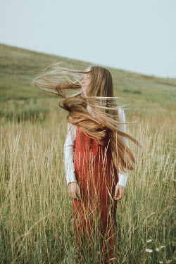 Alina Zhidovinova YOUNG BLONDE WOMAN TOSSING HAIR IN COUNTRYSIDE Women