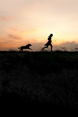 Yolande de Kort SILHOUETTE OF GIRL AND DOG RUNNING AT SUNSET Children