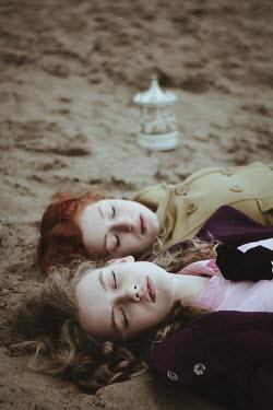 Alina Zhidovinova TWO YOUNG WOMEN LYING ON SANDY BEACH Groups/Crowds