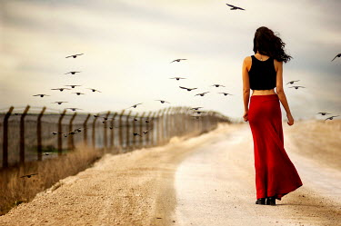 Metin Demiralay WOMAN STANDING ON ROAD SURROUNDED BY BIRDS Women