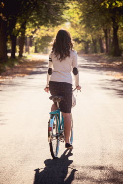Elisabeth Ansley YOUNG WOMAN CYCLING ON TREE LINED ROAD Women