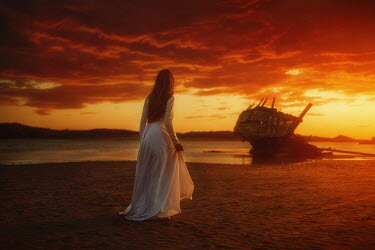 Terrence Drysdale HISTORICAL WOMAN NEAR SHIPWRECKED BOAT AT SUNSET Women