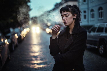 Renee Quost YOUNG WOMAN SMOKING BY CARS AT NIGHT Women