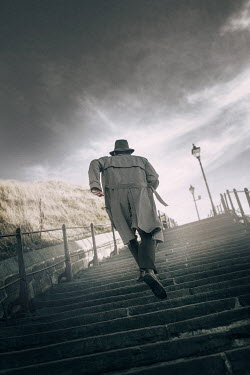 Laura Ranftler MAN IN COAT AND HAT RUNNING UP STEPS NEAR CLIFF Men