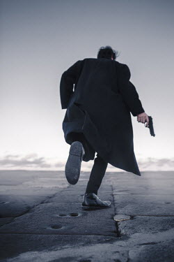 Laura Ranftler MAN IN BLACK COAT RUNNING WITH GUN Men