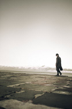Laura Ranftler MAN IN HAT AND COAT WALKING ON SEA WALL Men
