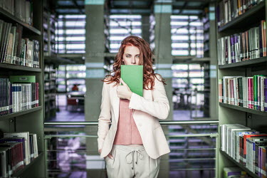 Vanesa Munoz YOUNG WOMAN HOLDING BOOK IN LIBRARY Women
