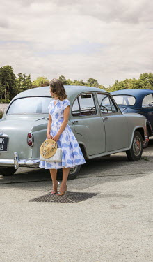 CollaborationJS young vintage woman standing by classic cars Women