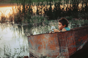Felicia Simion BOY SITTING IN RUSTY BOAT BESIDE LAKE Children