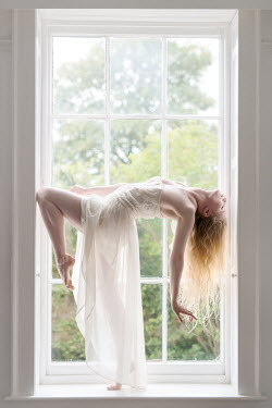 Rebecca Knowles YOUNG BLONDE WOMAN BALANCING BY WINDOW Women