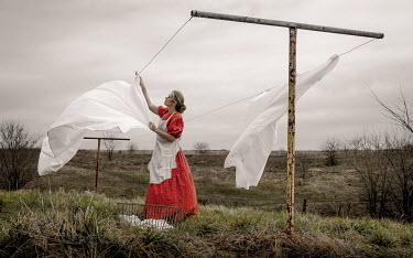 Rodney Harvey HISTORICAL WOMAN BY WASHING LINE IN FIELD Women