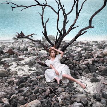 Igor Burba YOUNG WOMAN LYING ON ROCKS BY SEA Women