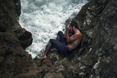Igor Burba MAN LYING ON ROCKS BY CHOPPY SEA Men