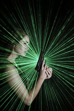 Stephen Carroll YOUNG WOMAN WITH GUN IN GREEN LIGHT BEAMS Women