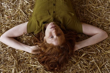 Marta Bevacqua YOUNG WOMAN WITH FRECKLES LYING ON STRAW Women