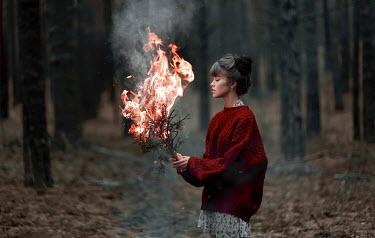 Igor Burba YOUNG WOMAN BURNING TWIGS IN FOREST Women