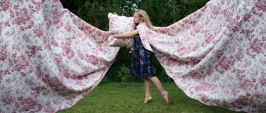 Efim Shevchenko YOUNG WOMAN HOLDING BED SHEETS IN GARDEN Women