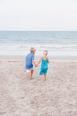 Erika Masterson BROTHER AND SISTER PLAYING ON BEACH Children