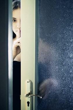 Ildiko Neer young woman with finger on lips behind door Women