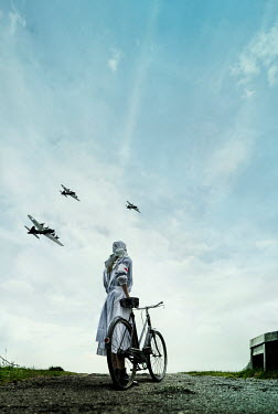 CollaborationJS WW2 nurse with bicycle looking at planes Women