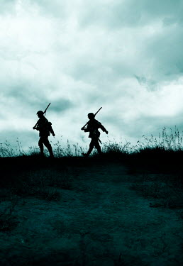 Stephen Mulcahey silhouette of two soldiers marching in field Groups/Crowds
