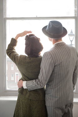 Lee Avison 1940s couple looking out of a sash window Couples