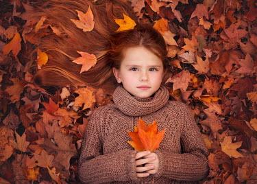 Lisa Holloway LITTLE GIRL LYING ON AUTUMN LEAVES Children