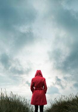 Stephen Mulcahey woman wearing red coat in long grass Women