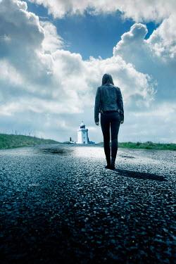 Stephen Mulcahey modern woman walking towards a lighthouse Women