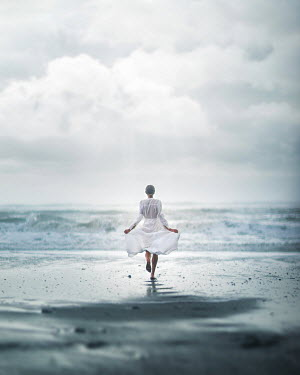 Dan Tidswell WOMAN IN WHITE DRESS RUNNING ON BEACH Women