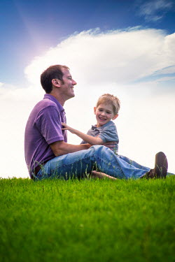 Elisabeth Ansley HAPPY FATHER AND SON SITTING IN FIELD Groups/Crowds