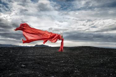 Dan Tidswell WOMAN WEARING RED DRESS IN WINDY LANDSCAPE Women