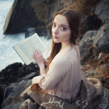Paulo Dias YOUNG WOMAN READING BOOK ON CLIFF EDGE Women