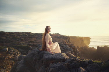 Paulo Dias WOMAN WITH LONG HAIR SITTING ON CLIFF EDGE Women