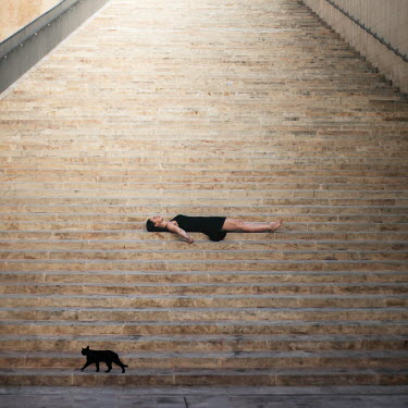 Michal Zahornacky YOUNG WOMAN LYING ON TALL CITY STEPS Women