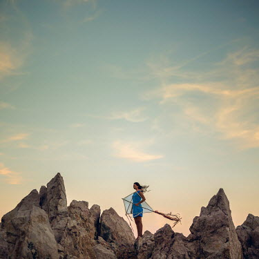 Michal Zahornacky YOUNG WOMAN WITH KITE STANDING ON ROCKS Women