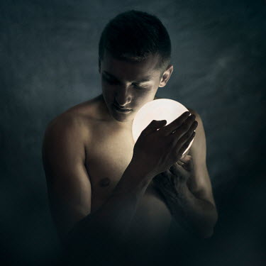 Michal Zahornacky MAN WITH BARE TORSO HOLDING LAMP IN SHADOWS Men
