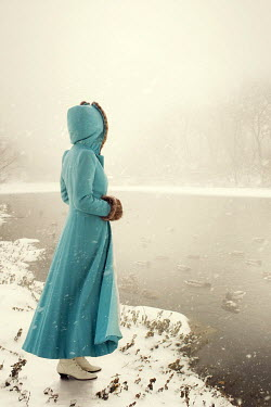 ILINA SIMEONOVA VINTAGE WOMAN WEARING BLUE COAT BY SNOWY LAKE Women