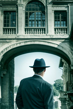 CollaborationJS 1940s man in hat under arched building Men
