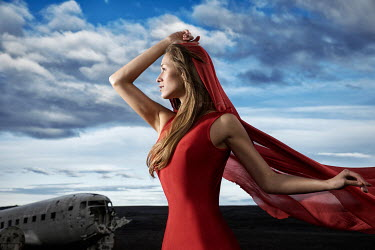 Dan Tidswell YOUNG WOMAN IN RED DRESS BY PLANE WRECK Women